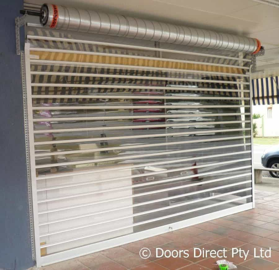 Aluminium roller shutter with clear inserts on shop front